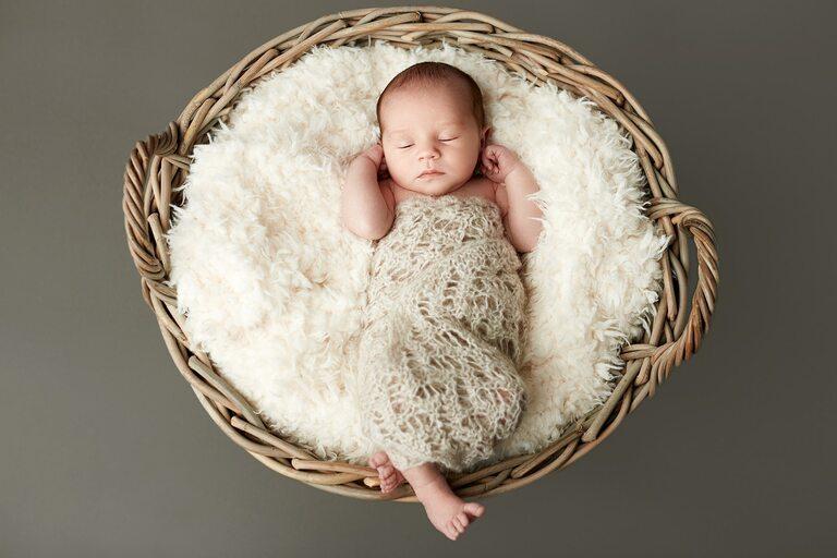 Ein Baby liegt in einem geflochtenen Korb auf einem Fell