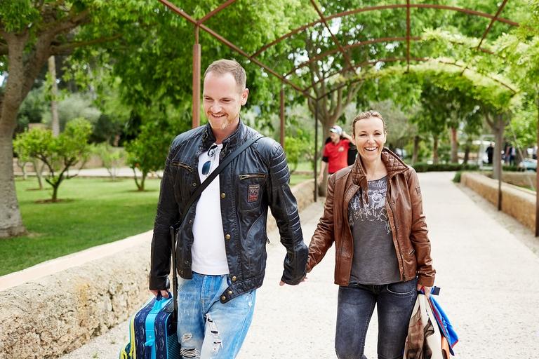 Ein Mann und eine Frau laufen händchenhaltend einen Weg entlang