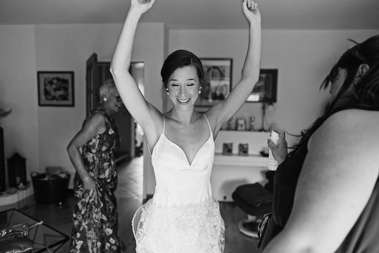 Eine Braut mit erhobenen Armen wird mit Deo besprüht von ihrer Trauzeugin