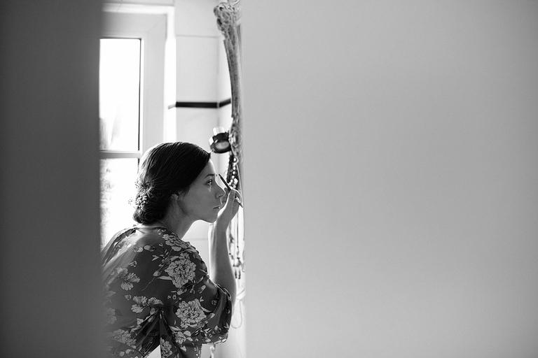 Eine Braut mit dunklen Haaren zieht sich einen Liedstrich vorm Spiegel