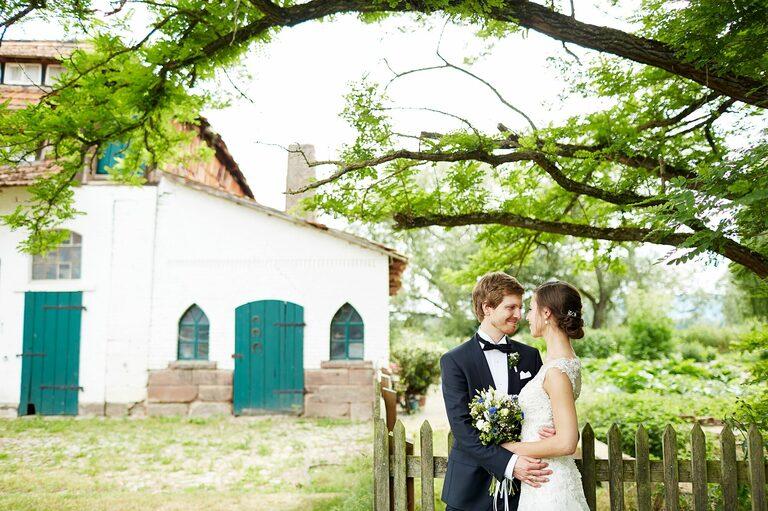 Ein Brautpaar steht an einem Holzzaun