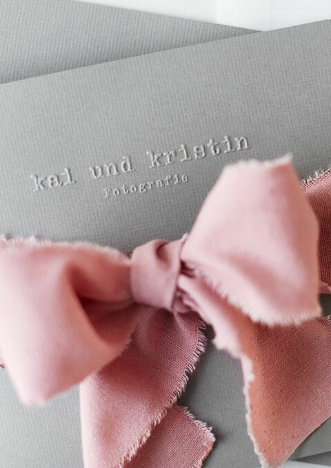 Ein Detail eines Gutschein von Kai und Kristin Fotografie mit rosa Schleife
