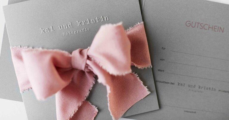 Ein grauer Gutschein von Kai und Kristin Fotografie mit rosa Schleife