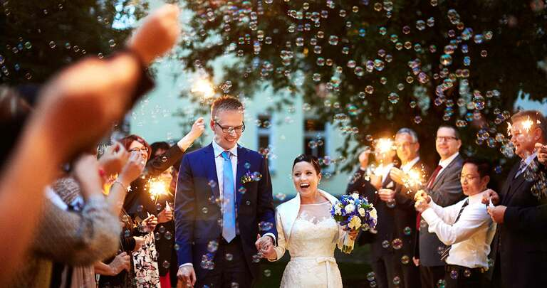 Ankunft eines Brautpaares und die Hochzeitsgesellschaft pustet Seifenblasen