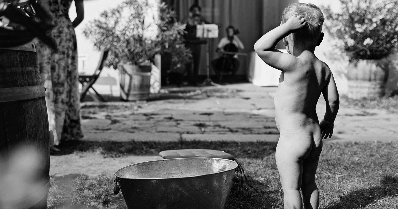Ein nackiger Junge steht an einer Badewanne und kratzt sich am Kopf
