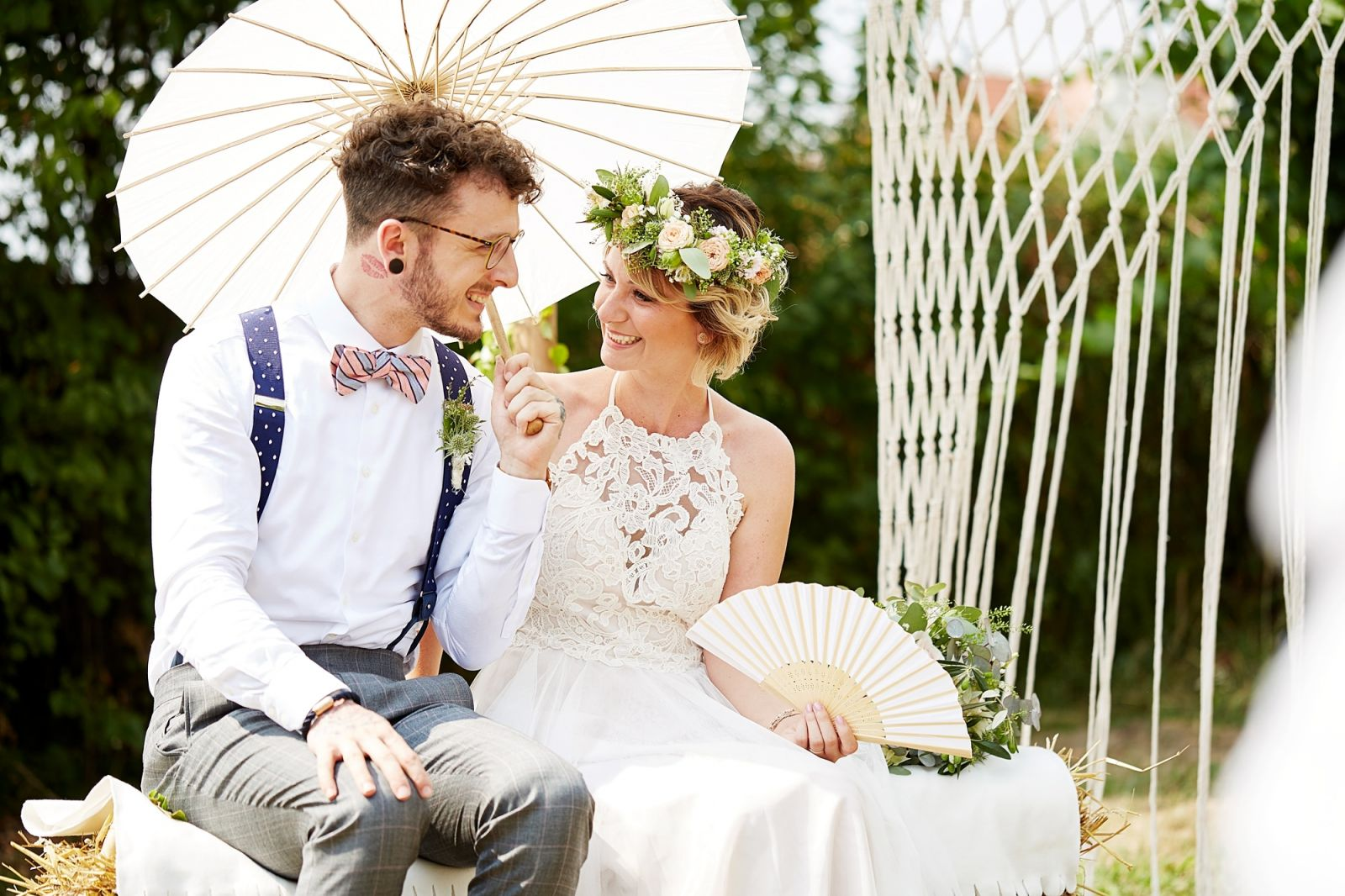 Brautpaar lacht sich verliebt unter Sonnenschirm an