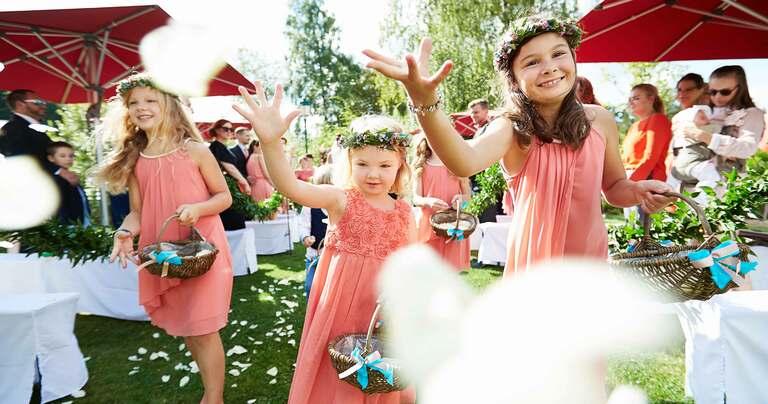 3 Blumenmädchen in rosafarbenen Kleidern streuen Blüten