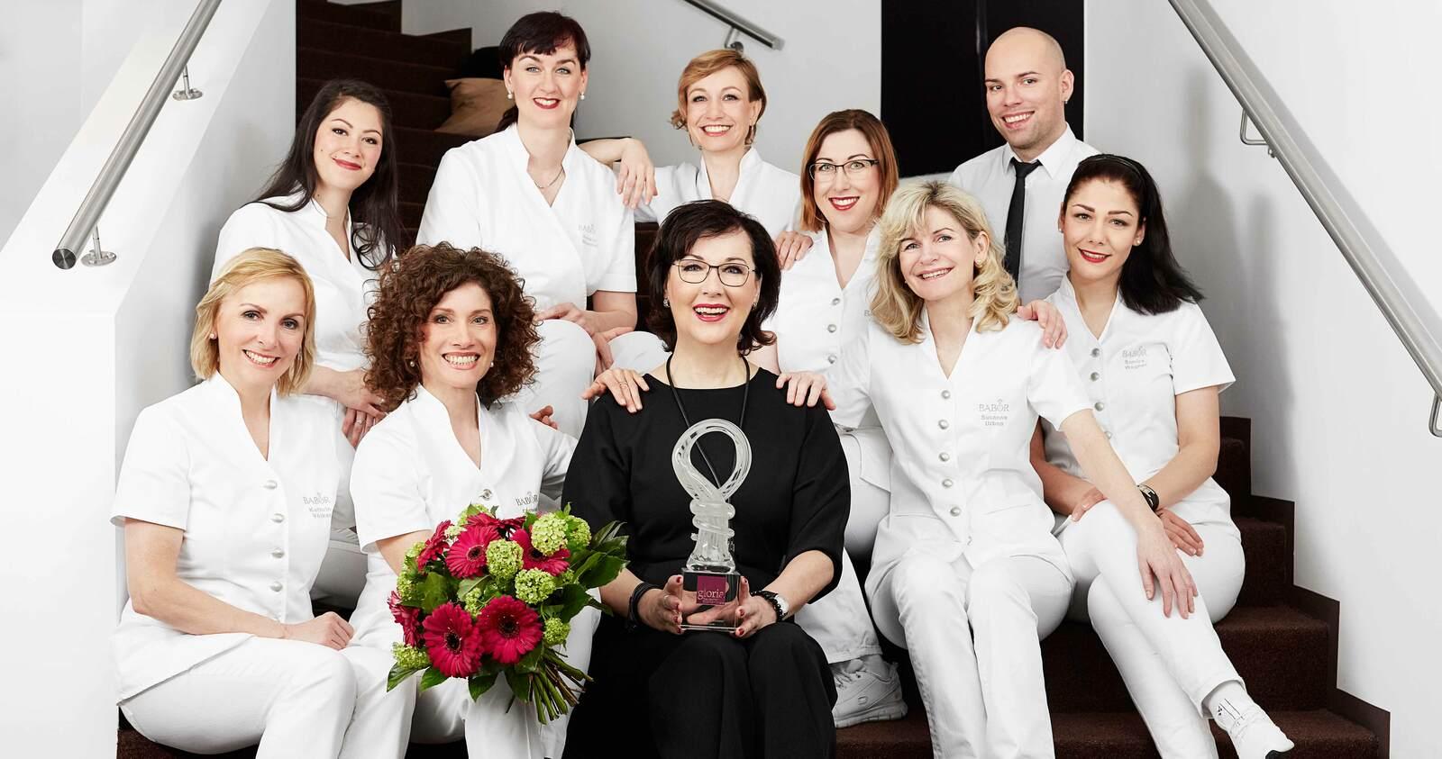 Gruppenbild von Kosmetikerinnen mit einem Pokal in der Hand