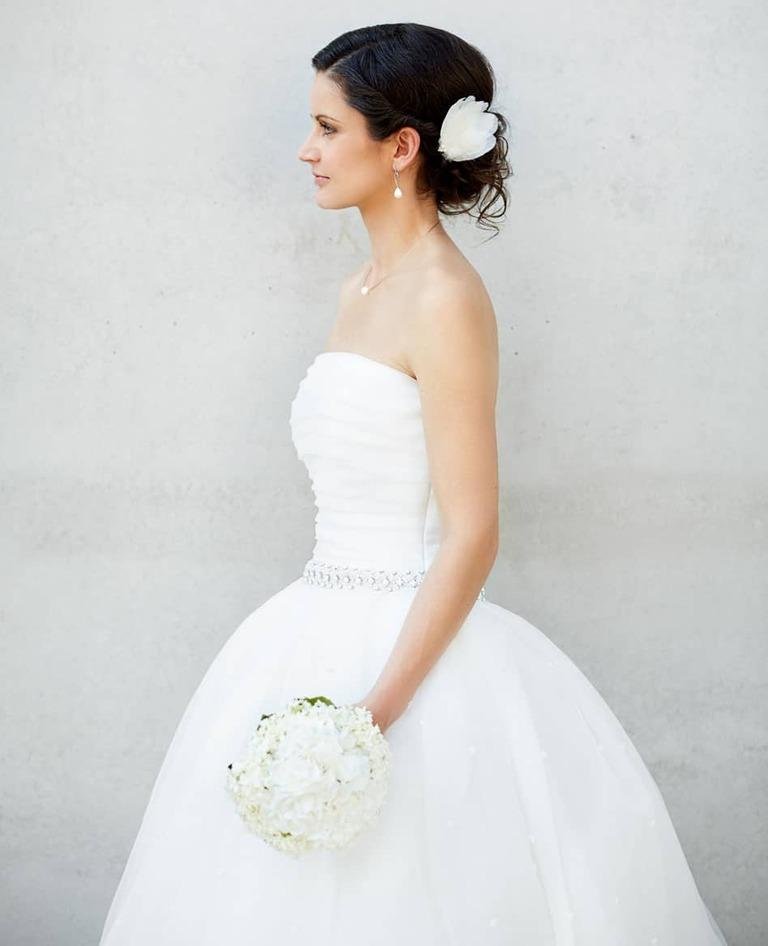 Eine Braut mit Brautstrauss vor einer Betonwand