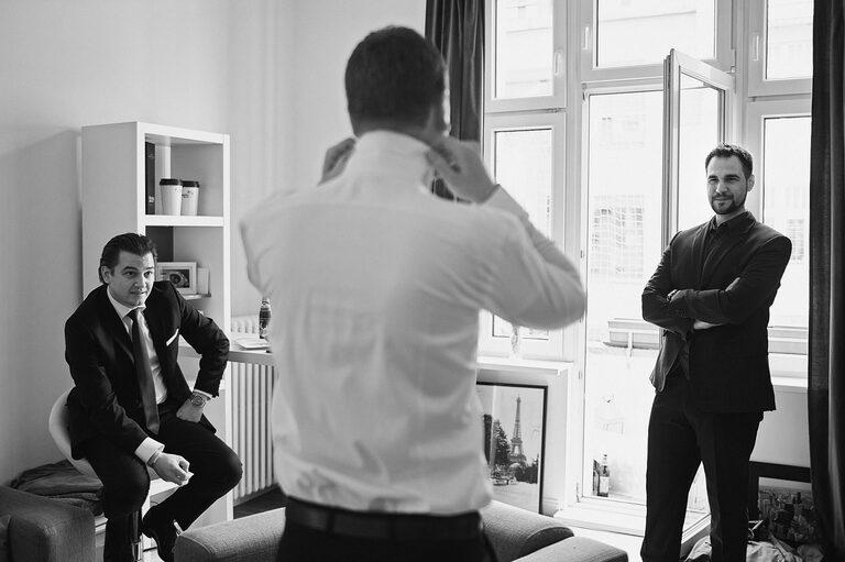 Ein Bräutigam richtet seinen Kragen vor zwei seinen Freunden