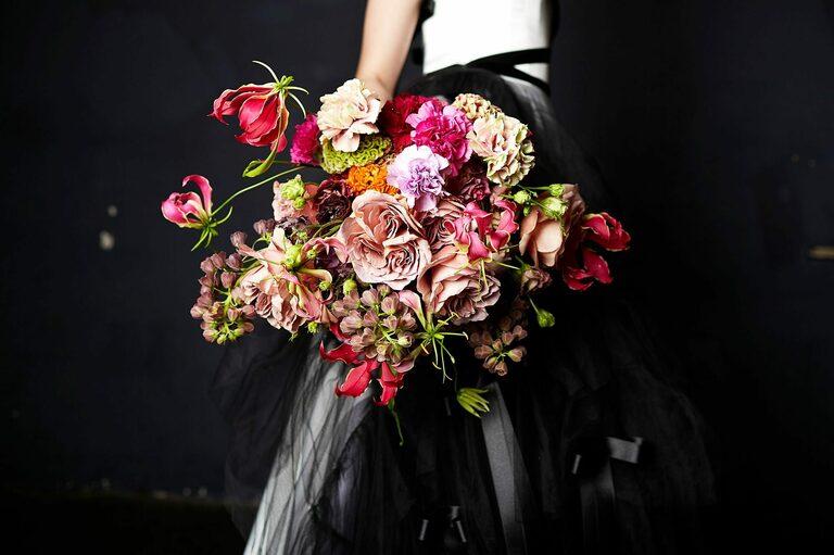 Ein Brautstrauß mit verschiedenen Blumen in Rot und Rosatönen
