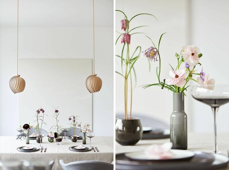 Eine Tischdekoration mit 2 Hängelampen und einem Bild im Hintergrund