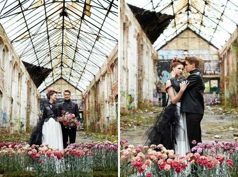 Ein Brautpaar steht zusammen in einer alten Industriehalle mit Glasdach
