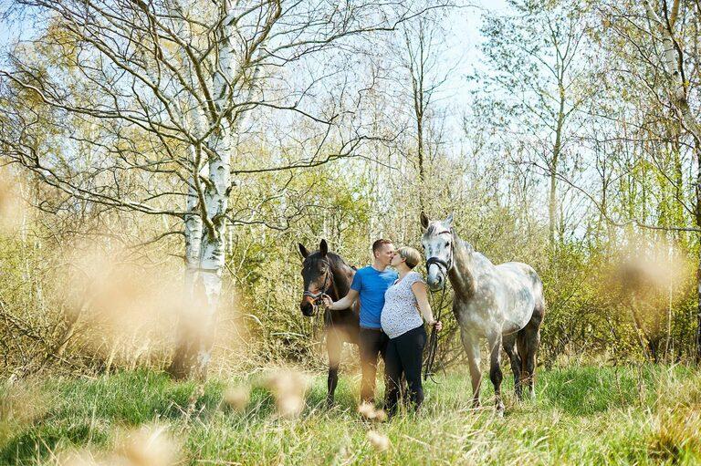 Eine Schwangere küsst ihren Partner in der Natur und beide halten jeweils ein Pferd an den Zügeln