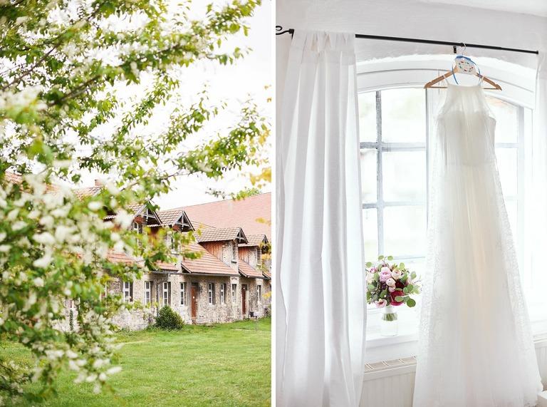 Das Brautkleid hängt an einer Gardinenstange und daneben steht der Brautstrauß auf dem Fensterbrett