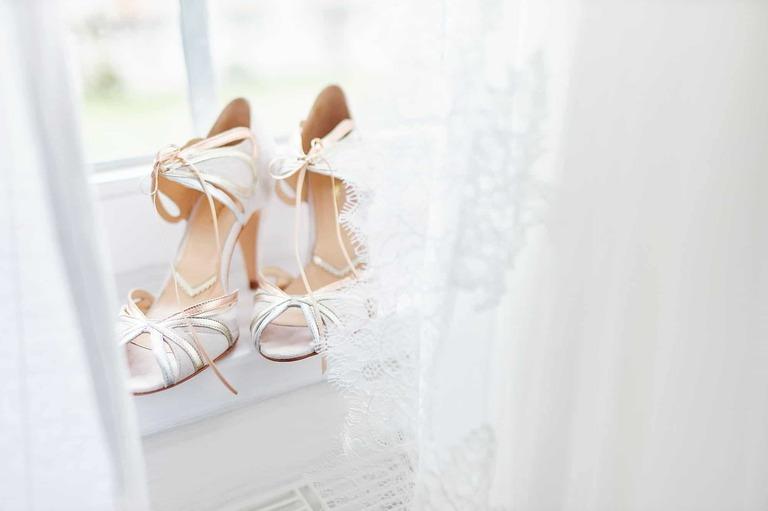 Vintage Brautschuhe stehen auf einer Fensterbank hinter dem Brautkleid
