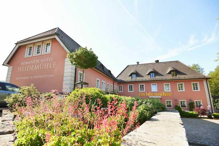Eine Außenaufnahme des Romantik Hotel Heidemühle mit Blumen im Vordergrund