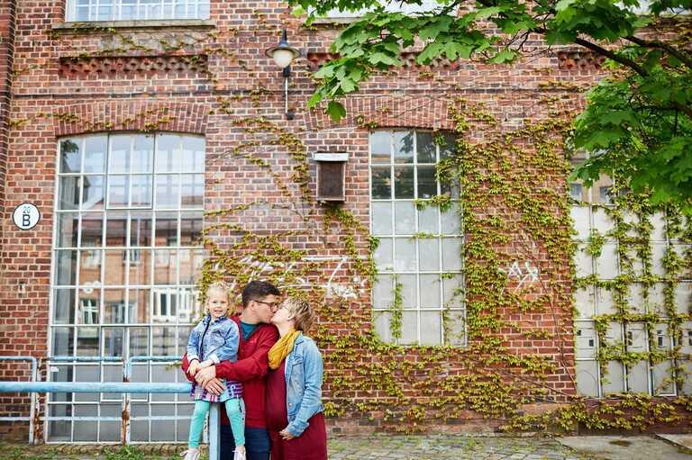 Eine Familie steht vor einer bewachsenen Backsteinwand mit weißen Sprossenfenstern