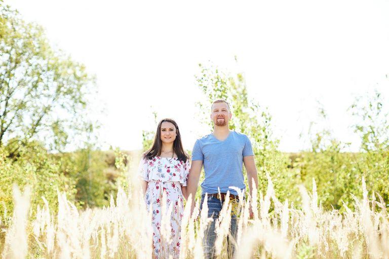 Ein hübsches Paar steht Hand in Hand zwischen Graspuschel und kleinen Birkenbäumen
