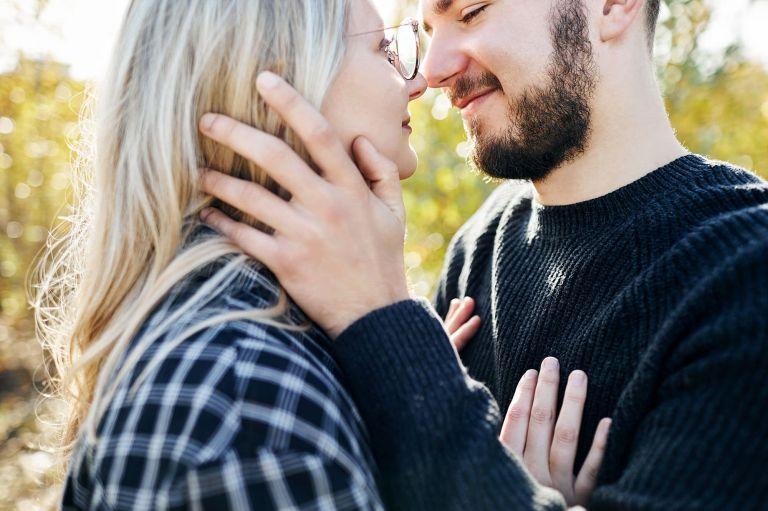 Ein Mann schaut seiner Freundin tief in die Augen während er ihr über die Wange streichelt