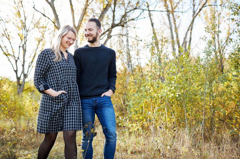Ein Paar spaziert durch den Wald und lacht