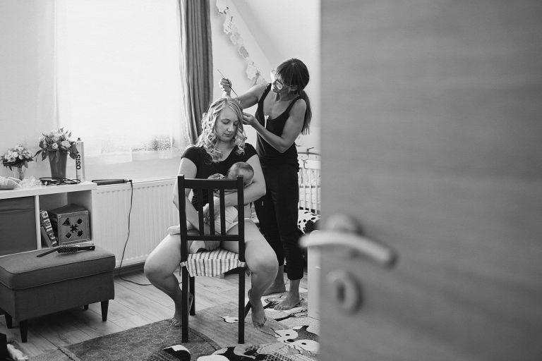 Eine Braut stillt ihr Baby während eine Friseurin ihr die Haare macht