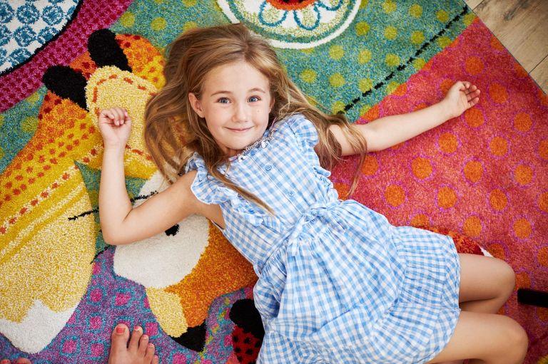 Ein Mädchen liegt auf einem bunten Teppich und schaut in die Kamera