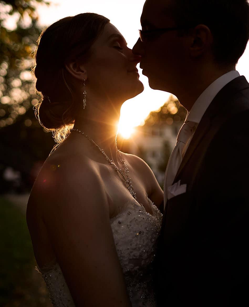 Ein Hochzeitsfotograf in Leipzig fotografiert ein küssendes Brautpaar im Sonnenuntergang