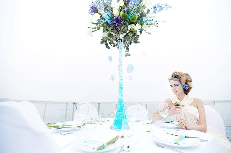 Eine Braut sitzt an einem gedeckten Tisch am Störmthaler See