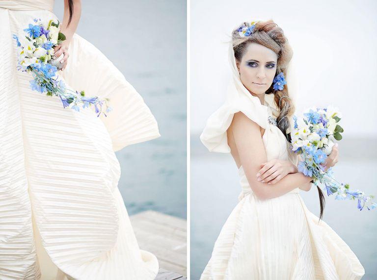 Ein Model posiert mit einem Brautkleid, einer aufwändigen Frisur und einem Brautstrauss mit blauen Blumen