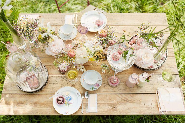 Eine frühlingshafte Tischdekoration auf einem Holztisch von oben
