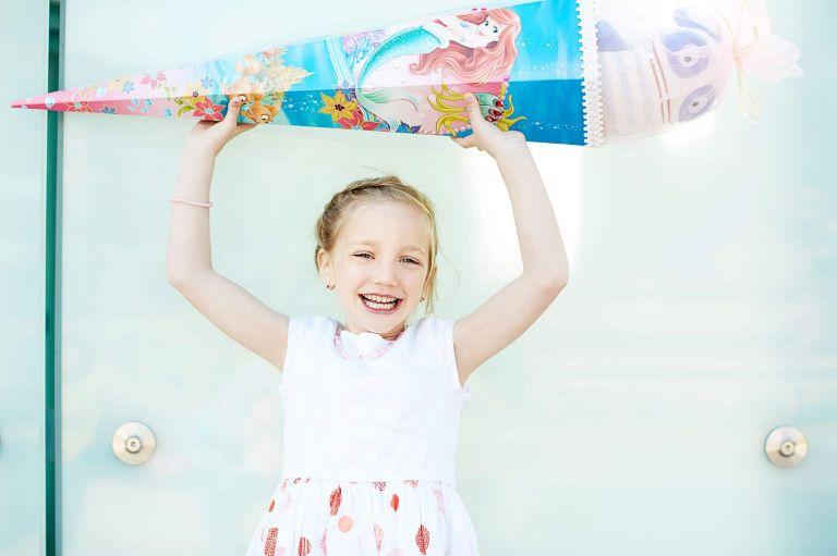 Ein Mädchen hält eine Arielle-Zuckertüte in die Luft und strahlt