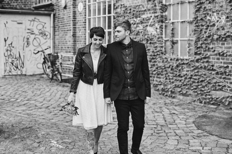 Ein frisch verheiratetes Pärchen spaziert für den Fotografen einem Weg entlang