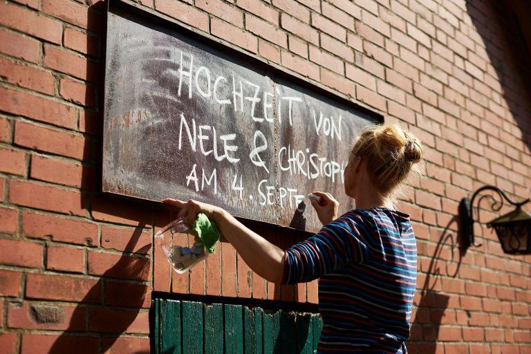 Eine Frau schreibt mit Kreide das Hochzeitsdatum an eine Tafel