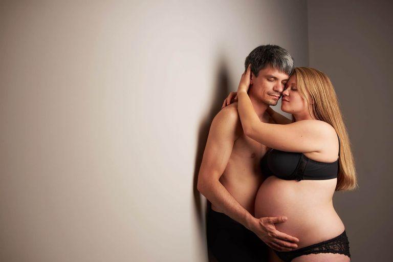 Ein Paar posiert bei einem Schwangerschaftsshooting in Leipzig mit geschlossenen Augen vor einem grauen Hintergrund