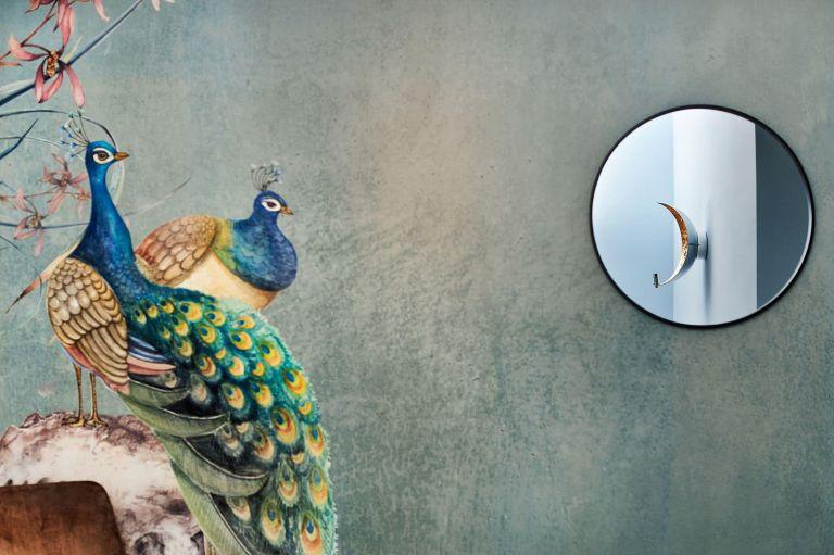 Eine Detailaufnahme einer Tapete mit Pfauen und ein Spiegel in dem sich eine Lampe spiegelt
