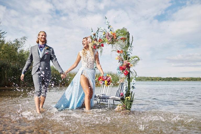 Ein Brautpaar spritzt spazierend Wasser in einem See festgehalten vom Hochzeitsfotograf Leipzig