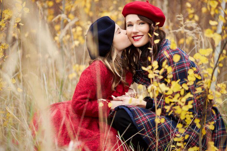 Eine Tochter gibt ihrer Mama einen Kuss auf die Wange
