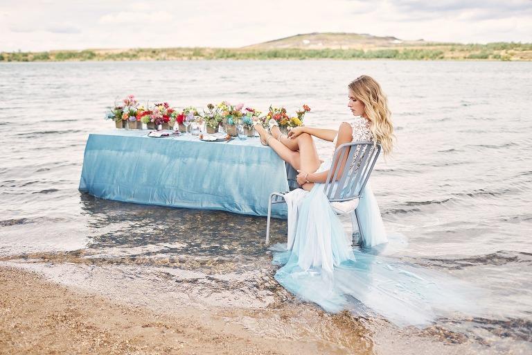Eine Braut sitzt auf einem Stuhl im Wasser und hat die Beine auf dem gedeckten Tisch