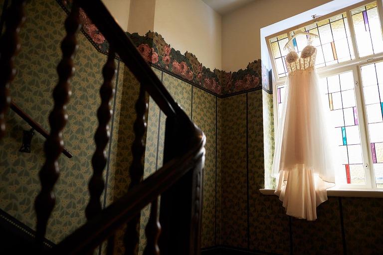 Ein Brautkleid hängt in einem alten Treppenhaus an einem Fenster